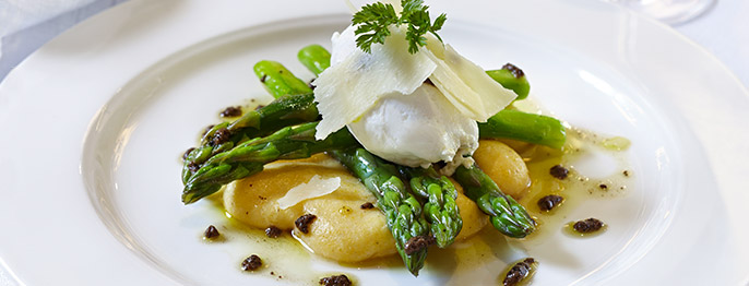 Asparagus spears artfully laid on top of creamy polenta and topped with cheese and herbs.