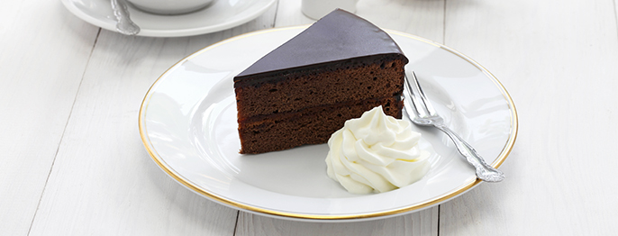 A slice of chocolate cake covered in a dark chocolate ganache, served with whipped cream on a white plate with gold rim.