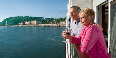 Elderly couple drinking wine on the veranda of their stateroom