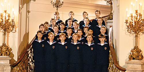The Vienna Boys Choir lined up on a staircase, all wearing matching black robes.