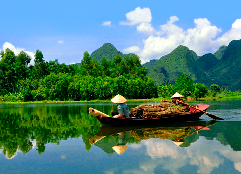Two boatmen navigate the Mekong River with green mountains and a bright blue sky.