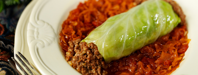 Green cabbage wrapped around ground meat served on top of bright red vegetable puree.