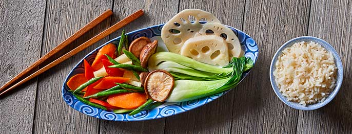Various vegetables including carrots, beans, bok choy, and more are served alongside a bowl of rice and chopsticks.
