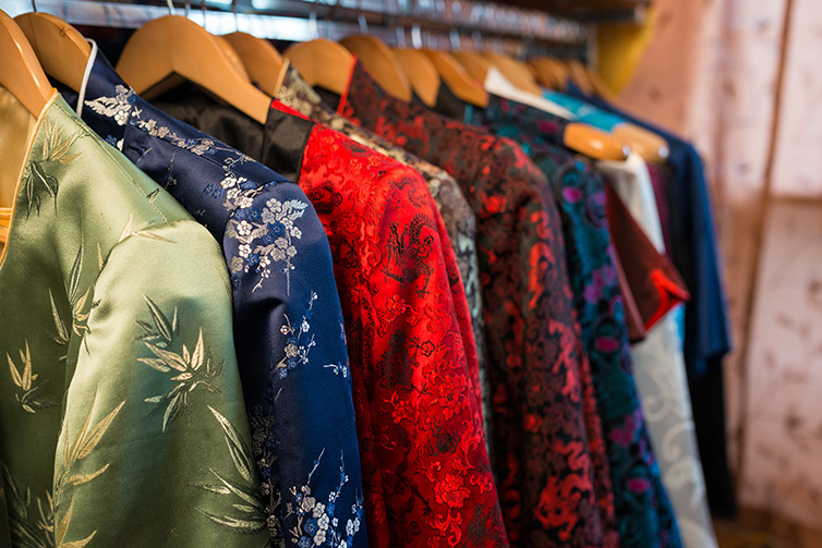 Colorful silk clothes hanging on rack
