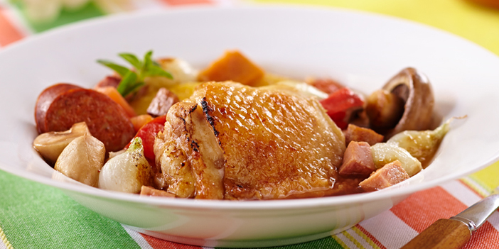 Crispy skin and sliced sausage emerge from a bowl of vegetables and sauce on a bright white bowl.