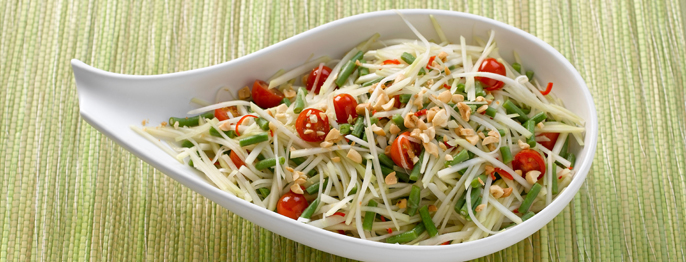 Shaved papaya salad served with nuts and tomatoes in a uniquely shaped white dish.
