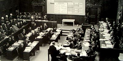 A black and white photo of a room full of desks and people at the Nuremberg Historic Trials.