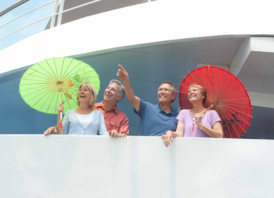 Mature couples with asian parasols on balcony aboard Viking Emerald