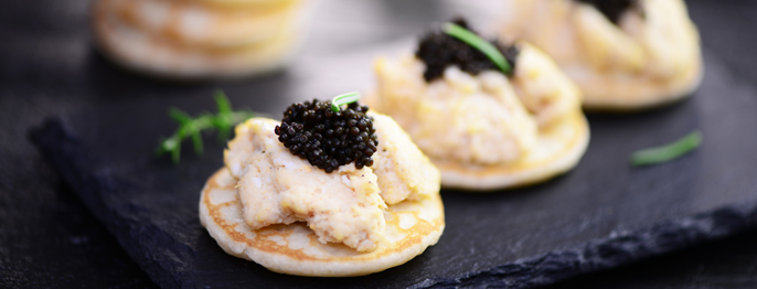 A pale pate sitting on a small pancake, topped with a dollop of dark black caviar.