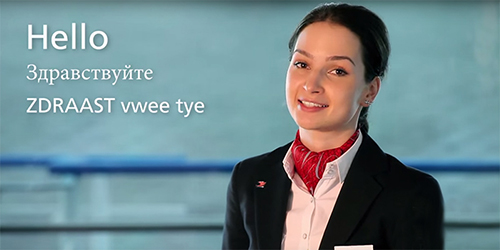 "A woman in a black blazer with the words ""Hello"" in English and Russian overlayed in white text."