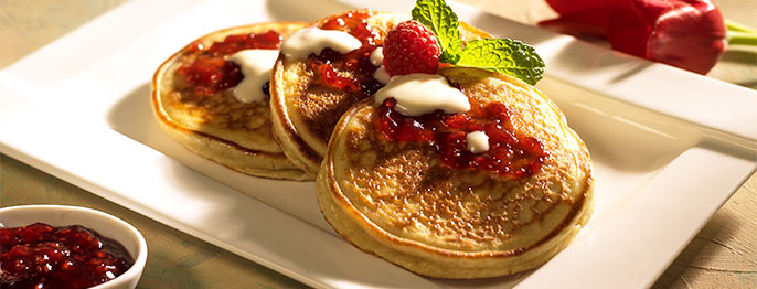 Three golden grilled pancakes on a rectangular plate topped with raspberry jam and a mint leaf.