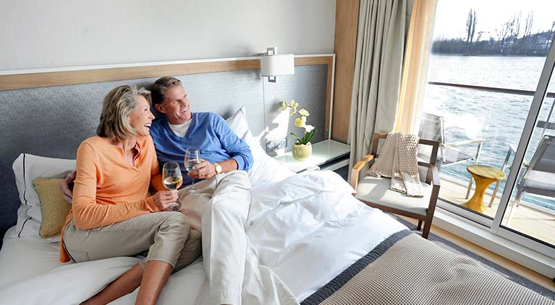 Couple enjoys wine in Veranda stateroom