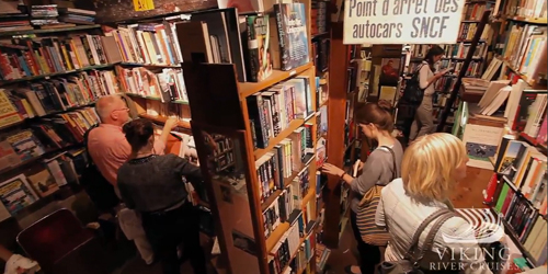 Bookshelves stuffed to the brim in an interior shot of a Paris bookstore called Shakespeare and Company