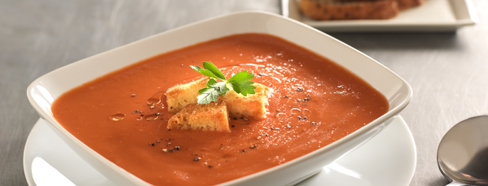 Creamy Tomato Soup with Truffle Oil, a red liquid with croutons and green garnish served in a white porcelian bowl.