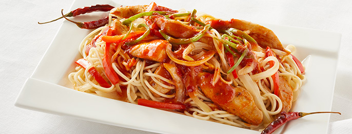 A rectangular plate full of red hot peppers, chicken, vegetables, and noodles.