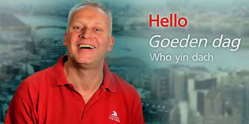 "A man wearing a red Viking shirt with the words ""Hello"" in English and Dutch overlayed in white text."