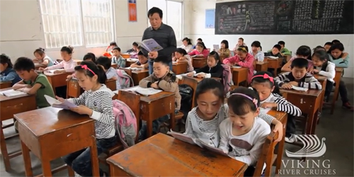 Schoolchildren in China reading from books in a classroom.