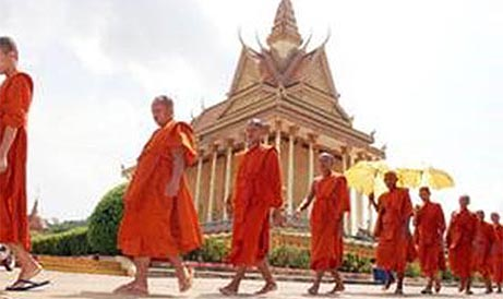 Orange robed Monks walking in a line with a temple in the background.
