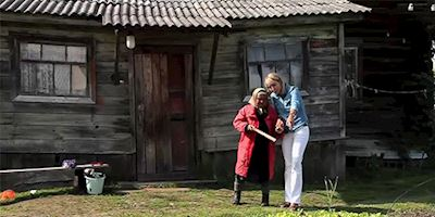 Karine Hagen outside a modest house with a small Russian woman